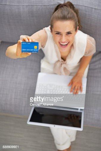 Feliz mulher jovem com laptop, mostrando o cartão de crédito : Foto de stock
