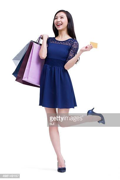 Happy young woman with shopping bags and credit card