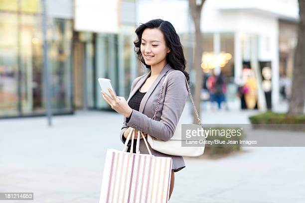 Happy young woman with shopping bags checking smart phone