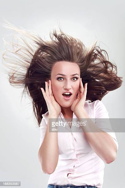 Happy young woman with wind in hair