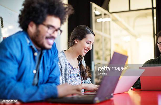 Happy young woman working on laptop with colleagues