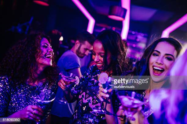 Happy young women enjoying cocktail in night club party