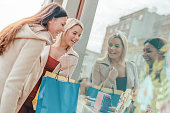 Shopping time. Happy women with shopping bags watching through the shop window. Consumerism, shopping, lifestyle concept