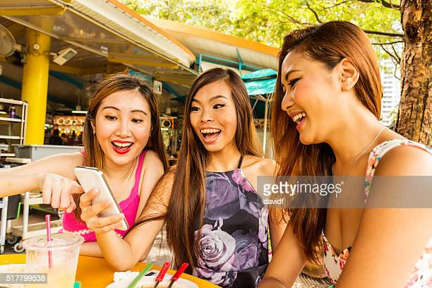 Happy Young Women in Singapore With a Mobile Phone