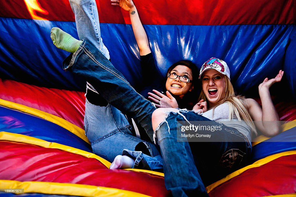Happy young women on a bouncy slide : Stock Photo