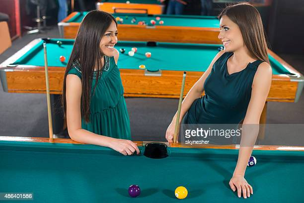 Happy young women playing billiard and talking.