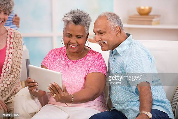 Hapy senior couple share information, video chat on digital tablet.