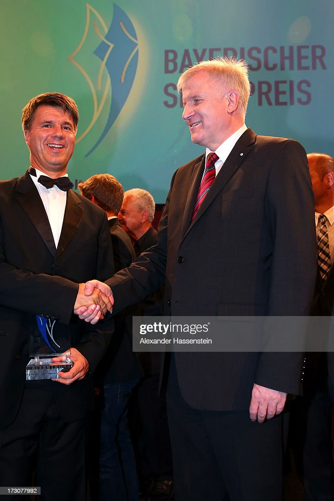 Harald Krueger, Board of Management member for Production of BMW AG poses with Bavarian state governor Horst Seehofer (R), after receiving the Bavarian Sportaward 2013 at the Bavarian Sport Award gala at BMW Welt on July 6, 2013 in Munich, Germany.