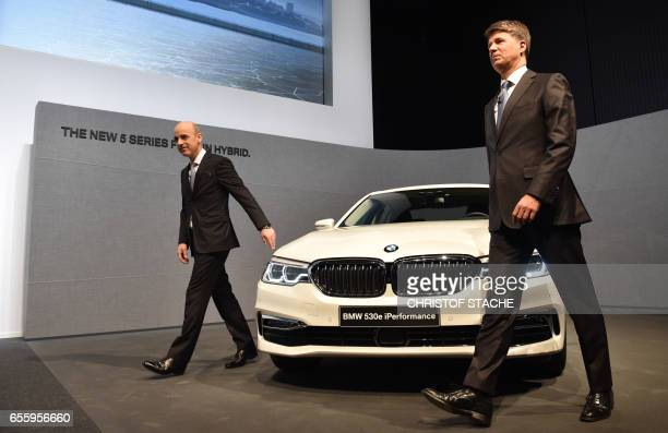 Harald Krueger CEO of German car maker BMW and Nicolas Peter the new CFO of German car maker BMW are pictured beside a new BMW 5 plugin hybrid car as...