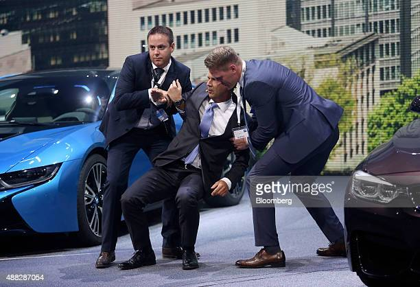 Harald Krueger chief executive officer of Bayerische Motoren Werke AG center is assisted after collapsing during a BMW press conference at the IAA...