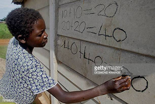 TO GO WITH AFP STORY 'ZIMBABWEECONOMYEDUCATION' Thirteenyearold Editor Muza writes mathematics on the wall of her family's makeshift home in...