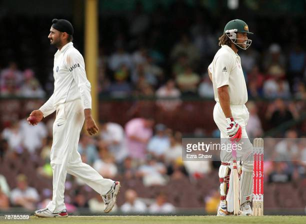 Harbhajan Singh of India walks past Andrew Symonds of Australia on his way back to his bowling mark during day four of the Second Test match between...