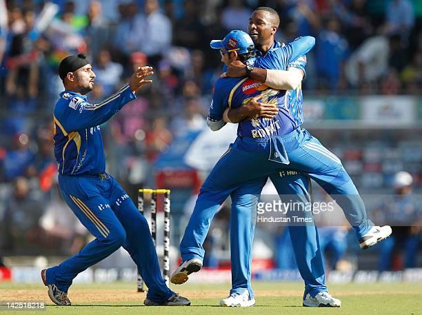 Harbhajan Singh Rohit Sharma and Kieron Pollard of the Mumbai Indians celebrate capturing the wicket of Callum Ferguson of the Pune Warriors during...