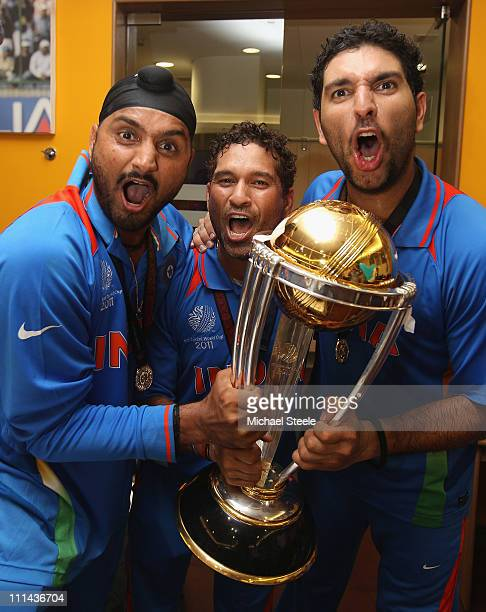 Harbhajan Singh Sachin Tendulkar and Yuvraj Singh with the winners trophy in the players dressing room during the 2011 ICC World Cup Final between...