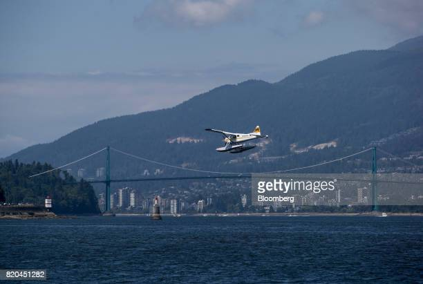 A Harbour Air seaplane prepares to land on the harbour past the Lions Gate Bridge in Vancouver British Columbia Canada on Tuesday July 11 2017...