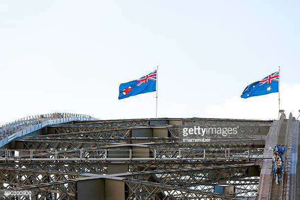 Harbour Bridge with Australian flags and climbing tourist, copy space