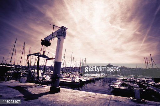 Harbour crane, moored boats and La Bonne Mere