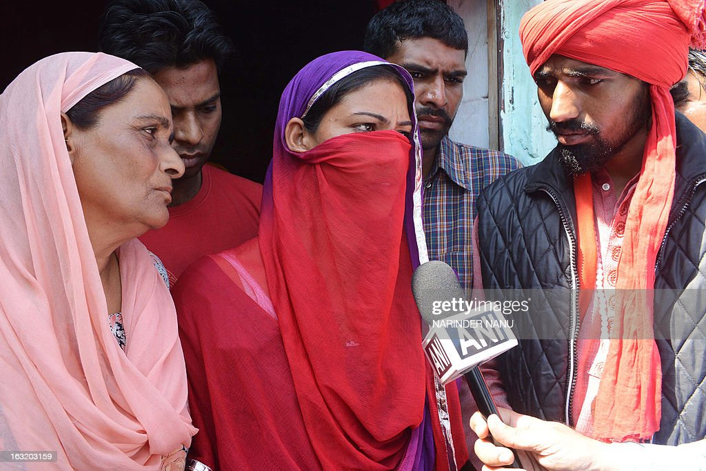 Harbrinder Kaur (C), 22, an Indian woman that was beaten by the police addresses the media at Usman village near Tarn Taran district about 25 kms (15 miles) from Amritsar on March 6, 2013. Taking serious view of the alleged beating of Kaur by policemen in Punjab's Tarn Taran district, Chief Minister Parkash Singh Badal today ordered a magisterial probe into the incident. The 22-year-old girl and her father were allegedly beaten by policemen when they sought to lodge a complaint against some persons who teased the girl and passed vulgar comments in public.