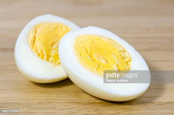 Hard boiled egg cut in half on chopping board