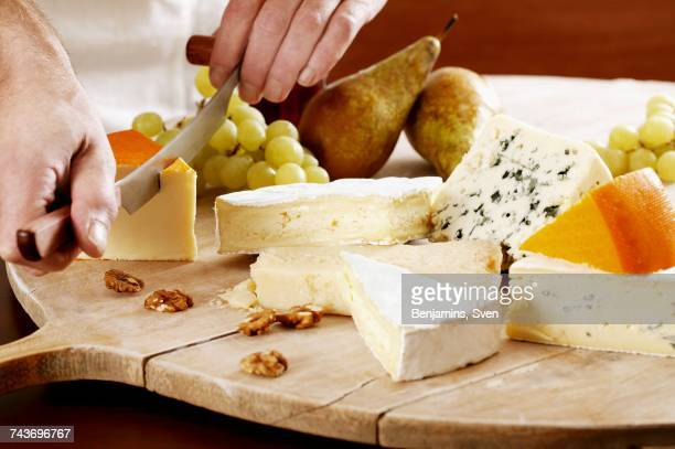 Hard cheese being sliced on a platter with various other types of cheese