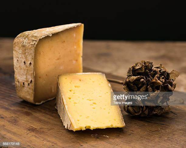 Hard cheese slices and truffle on wooden table, studio shot