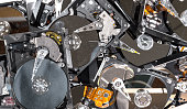 A pile of hard drives being recycled. The tops have been removed, and the drives are dusty and dirty. View is from the top.
