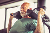 Active senior man using weights machine in the gym