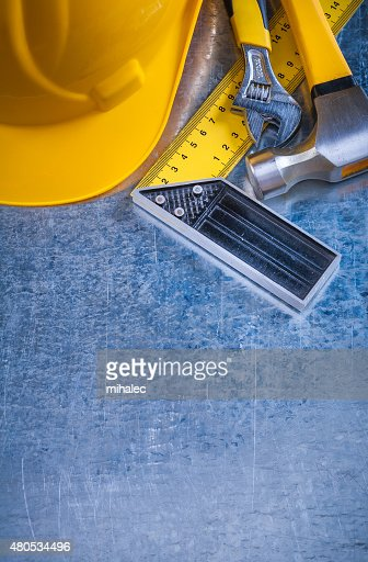 Hard hat claw hammer square ruler and adjustable spanner on : Stock Photo