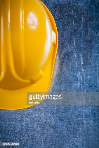 Hard hat on scratched vintage metallic background construction c : Stockfoto
