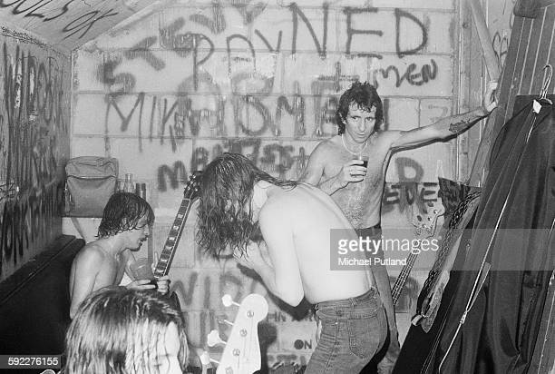 Hard rock group AC/DC backstage after a performance at the Marquee Club on Wardour Street London 11th August 1976 Singer Bon Scott is at far right On...