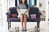 Part of beautiful young woman holding leather purse while sitting on sofa at the shoe store