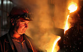 Hard work in the foundry, worker watching and controlling iron smelting in furnaces, too hot and smoky working environment