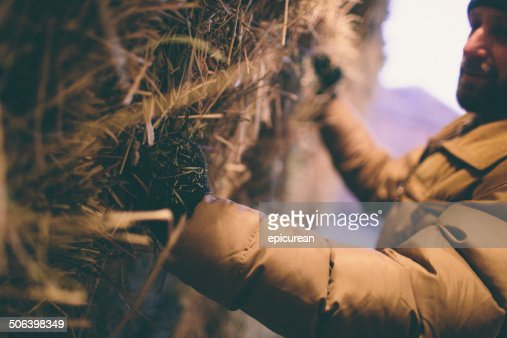 Hard working man grabs hay bale stacked in barn