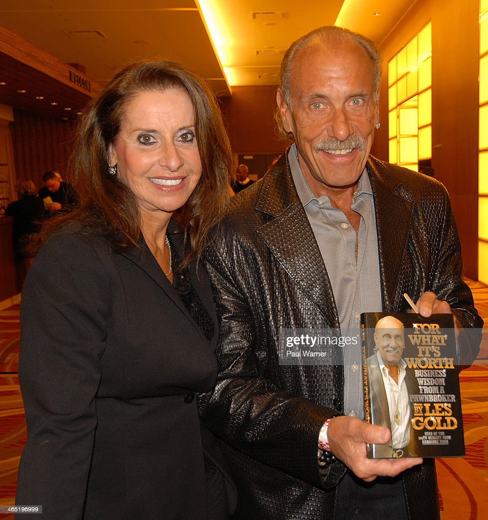 Hardcore Pawn castmember Les Gold (R) and his wife Lili pose with Les's book as theyattends Mittens for Detroit's 4th annual night of Giggles and Gloves at MGM Grand Hotel on January 25, 2014 in Detroit, Michigan.