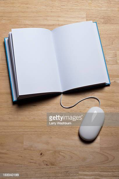 A hardcover book with a computer mouse attached to it