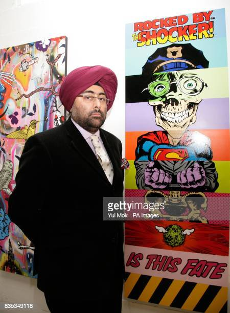 Hardeep Singh Kohli poses next to art by D*Face during a private view of the exhibition 'Artists 11' where 11 renowned urban artists have contributed...