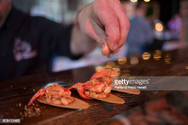Harding Lee Smith of the restaurant The Rooms sprinkles shallot pumpkin seed bread crumbs on lobster cassoulet at the Maine Lobster Chef Celebration...