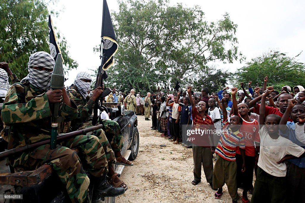 Hardline Islamist fighters from AlShabab parade past children as they rally in the streets of Mogadishu on October 30 2009 to show their support for...