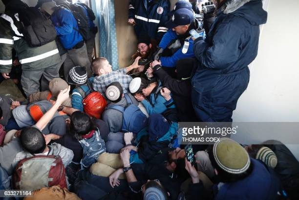 TOPSHOT Hardline Jewish settlers supporters of the Amona outpost northeast of Ramallah lock themselves together as security forces start to evict...