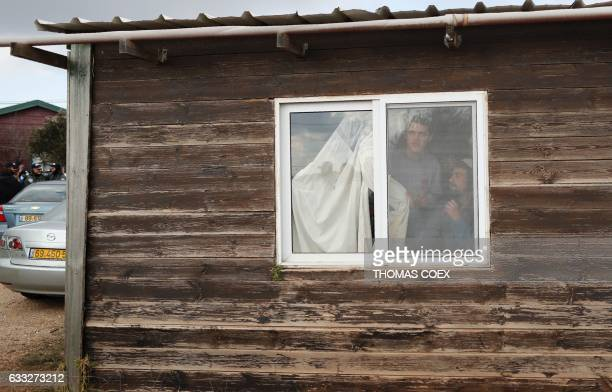 TOPSHOT Hardline Jewish settlers supporters of the Amona outpost northeast of Ramallah barricade themselves inside a building as security forces...