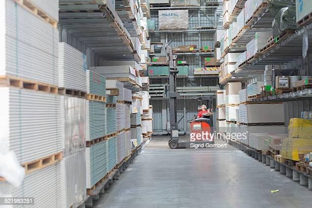 Hardware store warehouse worker moving stock in fork lift truck