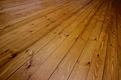 Light and dark brown oak colour stained natural wooden Pine floorboards.  The hardwood floor fills the frame, ideal for background use.  The grain is highly visible which has been enhanced by the use