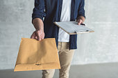This is for you. Close-up of envelope in hand of diligent professional courier. He is standing with package and personal contract against gray wall background. Selective focus