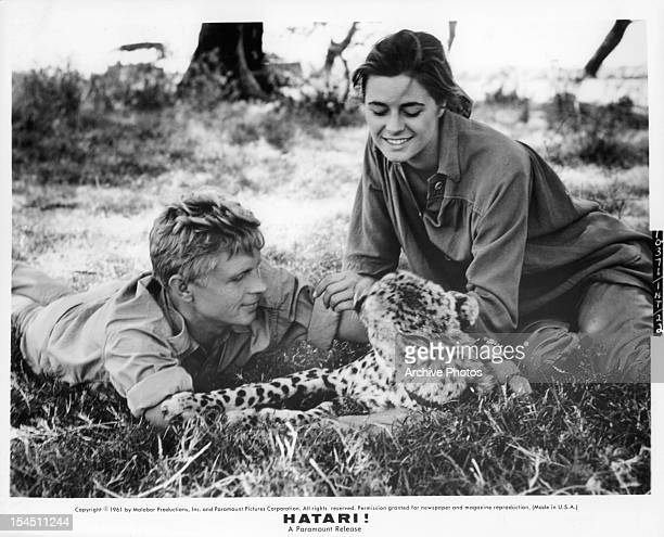 Hardy Krüger and Elsa Martinelli in the grass with wild cat on location in East Africa for the film 'Hatari' 1962