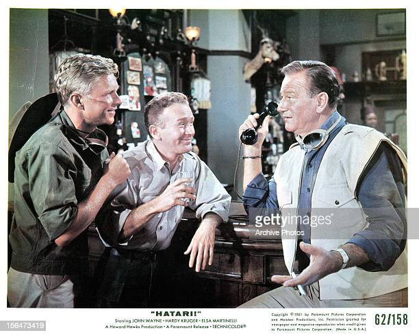 Hardy Krüger Red Buttons and John Wayne at a bar in a scene from the film 'Hatari' 1962