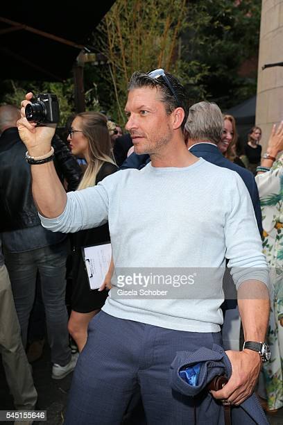 Hardy Krueger jr photographs during the Iris von Arnim by Unuetzer launch party of the cashmere sneaker at Bob Beaman Club on July 5 2016 in Munich...