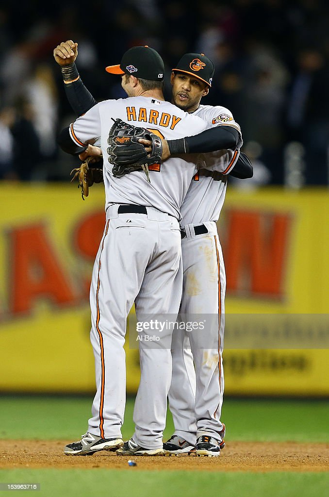 J.J. Hardy #2 of the Baltimore Orioles celebrates with teammate Robert Andino #11 after defeating the New York Yankees in thirteen innings in Game Four of the American League Division Series at Yankee Stadium on October 11, 2012 in the Bronx borough of New York City.