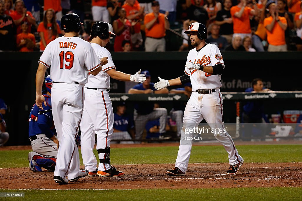 <a gi-track='captionPersonalityLinkClicked' href=/galleries/search?phrase=J.J.+Hardy&family=editorial&specificpeople=216446 ng-click='$event.stopPropagation()'>J.J. Hardy</a> #2 of the Baltimore Orioles celebrates with <a gi-track='captionPersonalityLinkClicked' href=/galleries/search?phrase=Travis+Snider&family=editorial&specificpeople=4959427 ng-click='$event.stopPropagation()'>Travis Snider</a> #23 and <a gi-track='captionPersonalityLinkClicked' href=/galleries/search?phrase=Chris+Davis+-+Baseball+-+Texas+Rangers&family=editorial&specificpeople=7129264 ng-click='$event.stopPropagation()'>Chris Davis</a> #19 after hitting a two RBI home run against the Texas Rangers in the seventh inning of their 4-2 win at Oriole Park at Camden Yards on July 1, 2015 in Baltimore, Maryland.