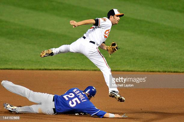 J Hardy of the Baltimore Orioles forces out Mike Napoli of the Texas Rangers as he slides into second base during the seventh inning of a baseball...