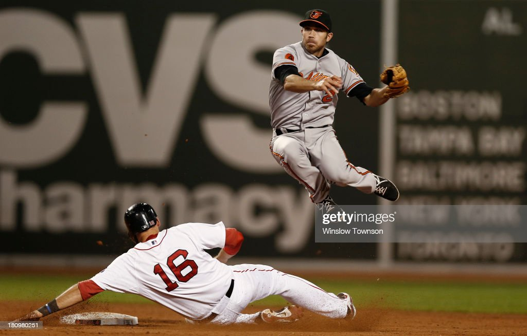 J.J. Hardy #2 of the Baltimore Orioles leaps over sliding Will Middlebrooks #16 of the Boston Red Sox to turn a double play during the eleventh inning of the game at Fenway Park on September 18, 2013 in Boston, Massachusetts.